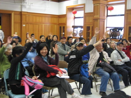 Fair participants with their hands raised in Woo's presentation